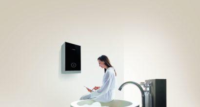 Woman wearing white bathrobe sitting on edge of modern bathtub and using digital tablet